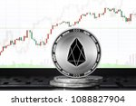 Small photo of EOS coin; EOS cryptocurrency on the background of the trading chart