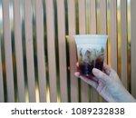 hand holding plastic glass of... | Shutterstock . vector #1089232838