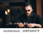 bearded man drinking in a bar | Shutterstock . vector #1089340379