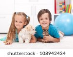 Stock photo happy kids with their pets a dog and a kitten laying on the floor 108942434