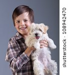 Happy boy holding his fluffy dog - best childhood friend - stock photo