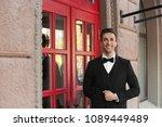 Young Doorman In Elegant Suit...