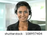 Portrait of a happy young Indian female call center employee with a headset. - stock photo
