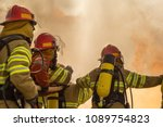 A Group Of Firemen Attacking A...