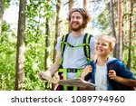 Small photo of Cheerful backpackers with map looking for place to settle down while walking through forest on summer day