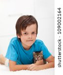Young boy holding his kitten - laying on the floor - stock photo