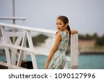 young girl standing near fence... | Shutterstock . vector #1090127996