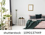 Stock photo white wall with molding in glamor bedroom interior with dirty pink bedding on the bed 1090137449