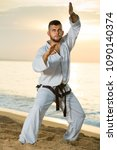 Small photo of Young man practising karate kata poses at seaside