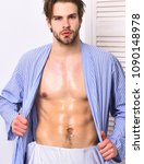 Small photo of Fit macho in bathrobe with torso and six packs.