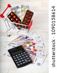 Small photo of Shopping cart with pills,money and calculator on a wooden background. Paid medicine.