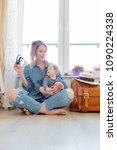Small photo of Young girl with little baby sitting next to suitcase before travel near a window at home