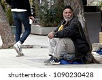 Small photo of An elderly Refugee man sits at the Victoria square, where hundreds of migrants and refugees stay temporarily in in Athens, Greece on Feb. 24, 2016.