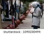 a refugee woman checks his... | Shutterstock . vector #1090230494