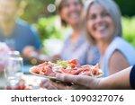 close up on a hand serving a... | Shutterstock . vector #1090327076