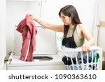 working woman adding clothes to ... | Shutterstock . vector #1090363610