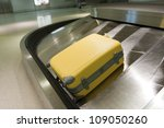Yellow suitcase on airport carousel - stock photo