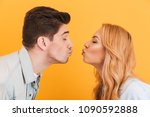 Small photo of Profile photo of young beautiful people in love expressing love and affection while kissing each other with closed eyes isolated over yellow background