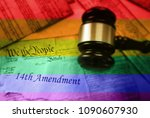 Small photo of Rainbow flag colors over 14th Amendment text on pages of the US Consitution and gavel
