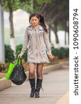 Small photo of GUANGZHOU-DEC. 13, 2013. Fashionable, pretty girl walks on the street. China has a traditional bias for sons. Many families abort female fetuses, so there are 118 boys are born for every 100 girls.