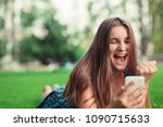 Small photo of Excited beautiful girl receiving a sms message with good news in a mobile phone outside in park lying down on green lawn trees on background. Multicultural model, mixed race asian russian teenage girl
