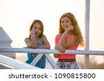 two teenagers girls sittihg on... | Shutterstock . vector #1090815800