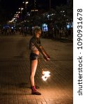 Small photo of Kyiv, Ukraine - 06 May, 2018: a young girl fakir in the center of the city arranges a fiery show.
