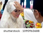 Small photo of Kuala Lumpur/ Malaysia - July 25th, 2015: Malay muslim wedding. The bridegroom touches the bride's forehead as a blessing and a form of loving touch between husband and wife. Ceremony was in a mosque.