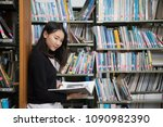 asian students in the library.... | Shutterstock . vector #1090982390