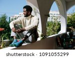 african man seating on balcony  ... | Shutterstock . vector #1091055299