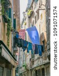 Small photo of Laundry drying in a narrow alley somewhere in Italy