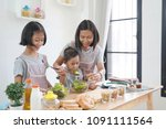 mother and daughter cooking in... | Shutterstock . vector #1091111564