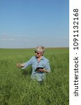 Small photo of Female agronomist or farmer examining green canola field, rapeseed plant in spring