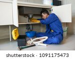 young plumber checking drain in ... | Shutterstock . vector #1091175473