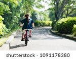 little girl playing with bicycle | Shutterstock . vector #1091178380