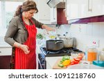 mature woman is cooking a curry ... | Shutterstock . vector #1091218760
