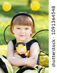 Small photo of happy little girl in a bee costume walking briskly in a sunny park with dandelions