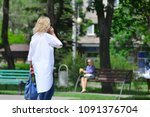 a woman walks and talks on a... | Shutterstock . vector #1091376704