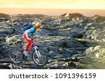 young tourist cycling on lava... | Shutterstock . vector #1091396159
