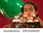 a girl blowing the candles | Shutterstock . vector #1091400020