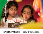 two girls blowing out candles | Shutterstock . vector #1091400308