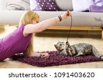 Stock photo girl playing with her cat 1091403620