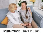 Small photo of Happy family. Cheerful blonde woman embracing her kid while being in all ears