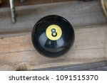 Small photo of A magic eight ball sits on a distressed wood texture with lots of room for text! Vintage magic 8 ball!