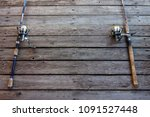 two fishing rods on wooden... | Shutterstock . vector #1091527448