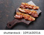 fried bacon on wooden cutting... | Shutterstock . vector #1091630516