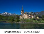 Picturesque Lofoten cathedral on Lofoten islands in Norway with snowy peaks in the background - stock photo