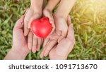 red heart in family hands on... | Shutterstock . vector #1091713670