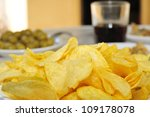 closeup of a plate whit potato chips on a table with other appetizers, as olives - stock photo