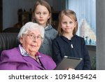 Small photo of 95-year-old woman and her 7-year-old and 9-year-old great-granddaughter look at the camera. She is sitting on a chair in her living room. The two girls are standing. The grandmother is holding a tabet